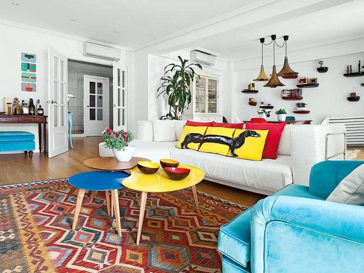 Яркие диванные подушки, синее кресло и разноцветный модульный столик
