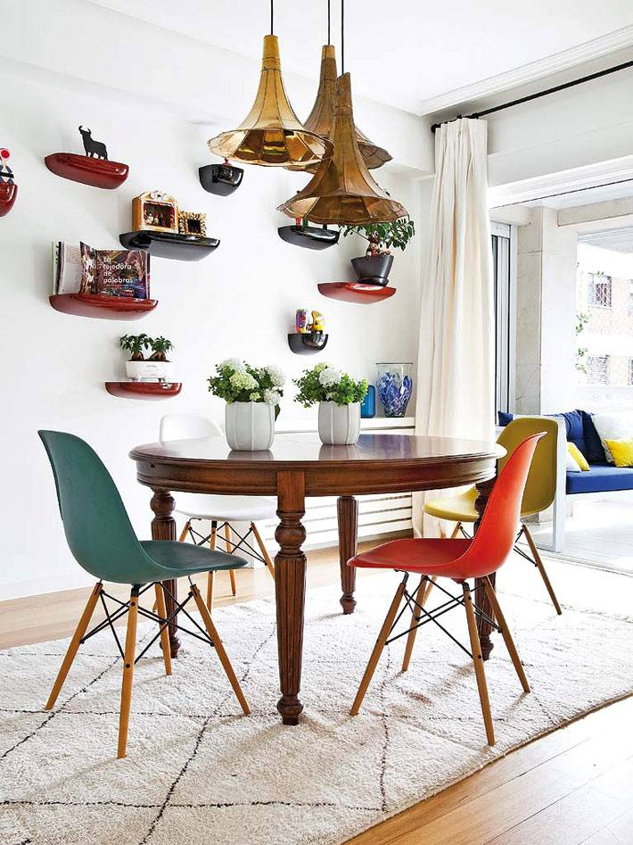 обеденная зона с круглым столом, разноцветными стульями и оригинальной люстрой