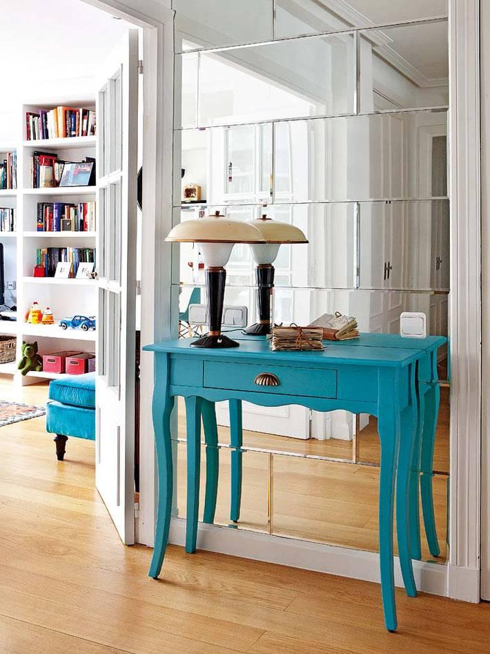 Консольный стол голубого цвета возле зеркальной стены в интерьере