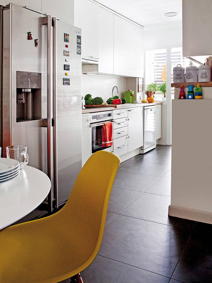 маленькая кухня белого цвета с обеденной зоной за круглым столом