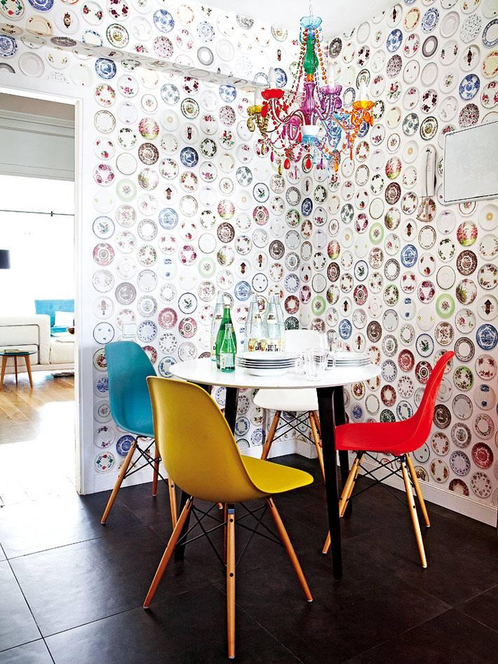 разноцветные стулья, пестрые обои и яркая люстра в интерьере