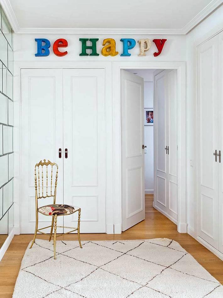 Надпись be happy на белой стене комнаты