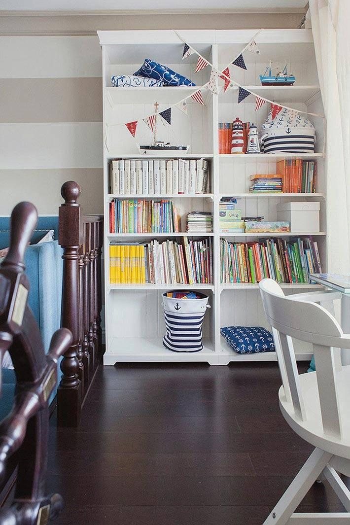 белый стеллаж для книг на подиуме в интерьере детской комнаты