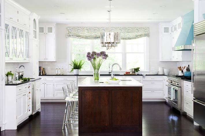большая белая кухня с коричневым островом посередине фото
