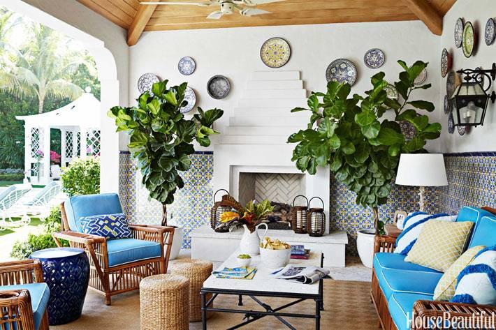 Веранда с камином, мягкими креслами и живыми растениями в кадках
