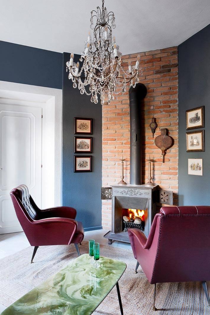 чугунная печь-камин с живым огнем в интерьере с синими стенами