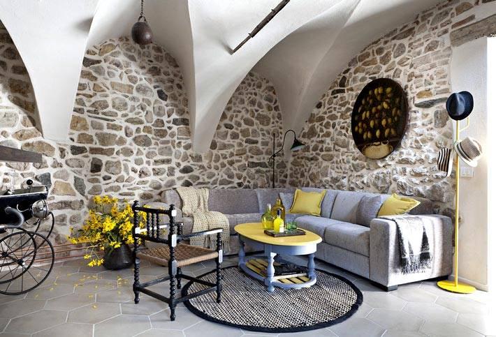потолок со сводами и стены из камня в дизайне гостиной комнаты
