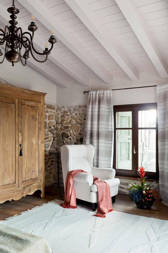 красивое белое кресло и старый шкаф в интерьере спальни