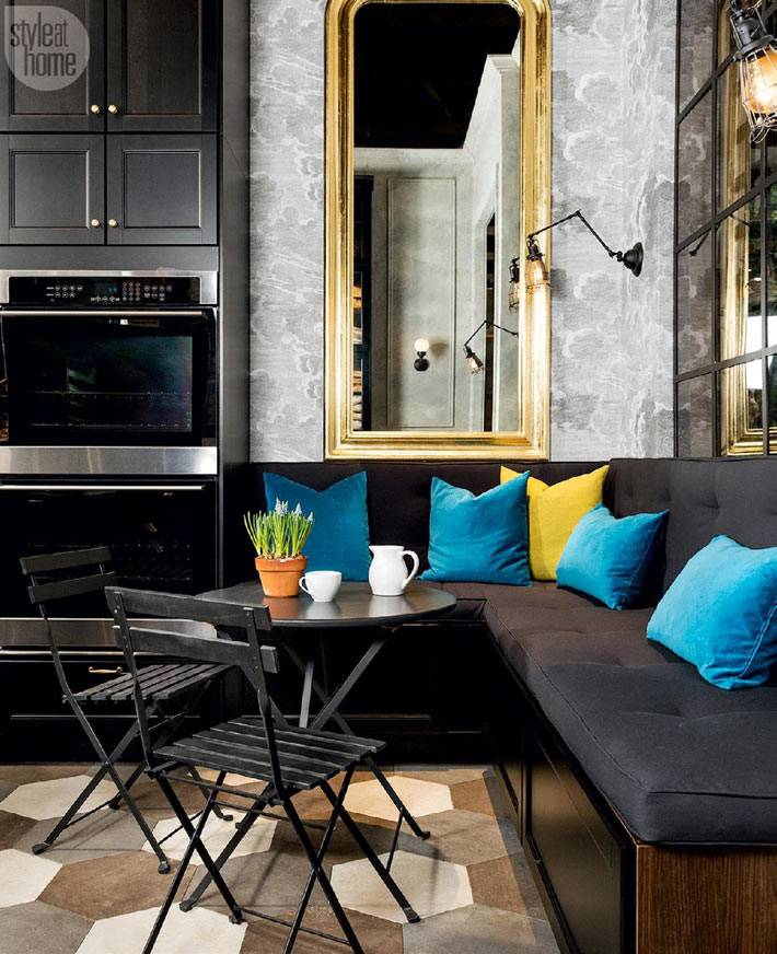 черный мягкий уголок возле круглого обеденного стола на кухне фото