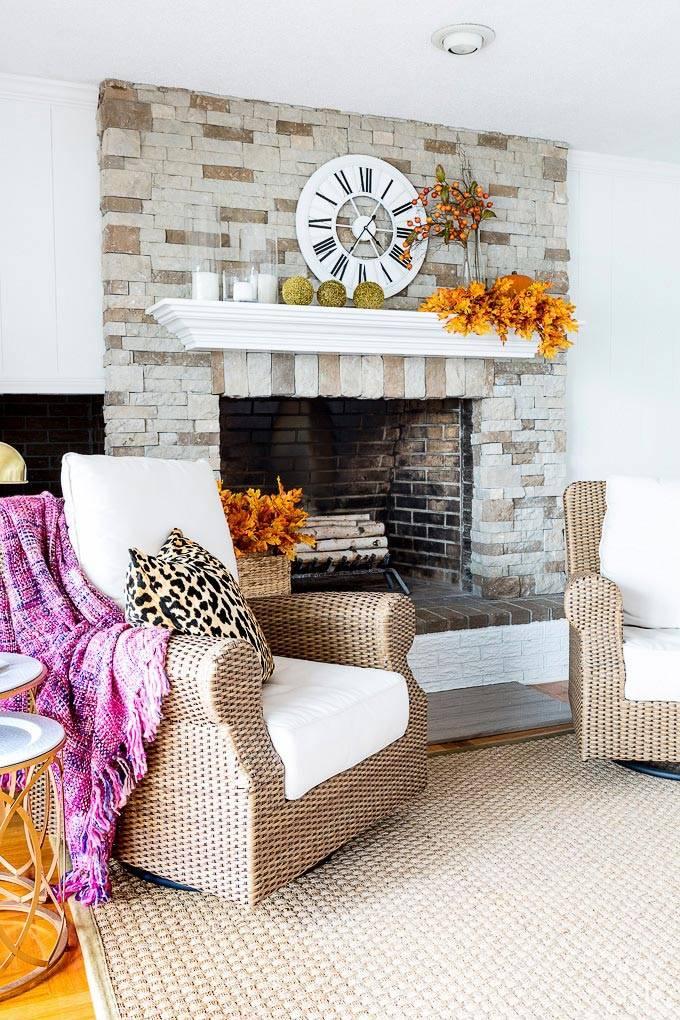 уютный интерьер комнаты с камином и красивым осенним декором