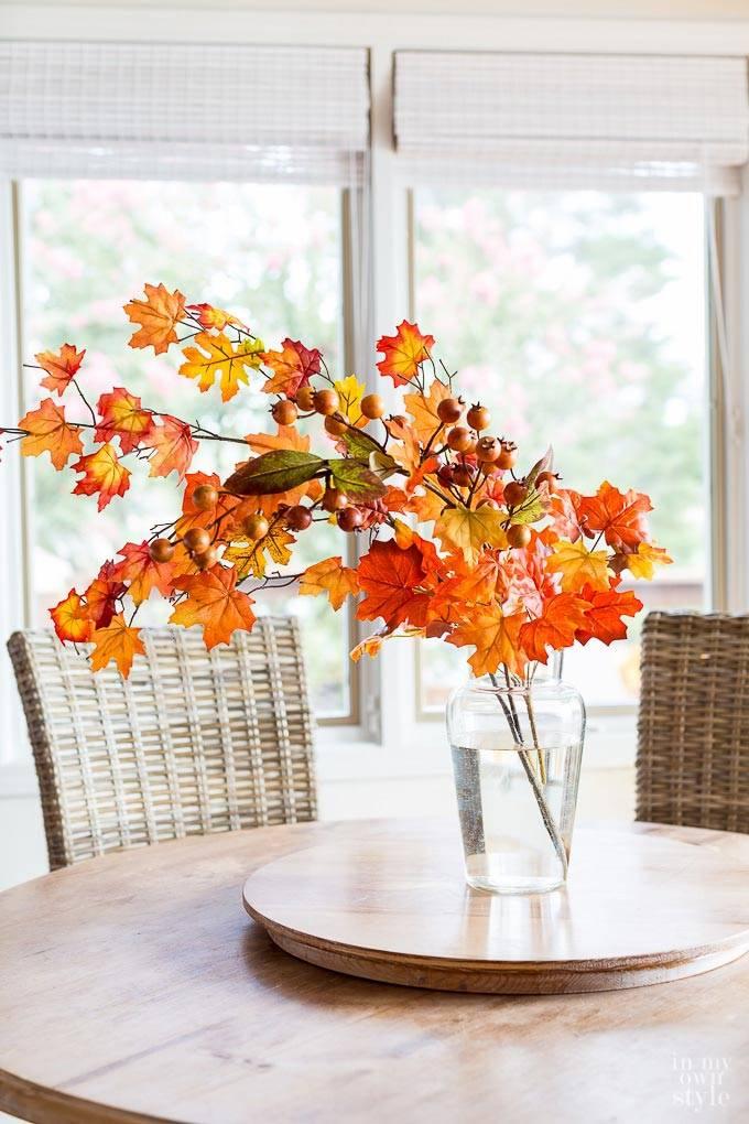 красивый букет из оранжевых осенних листьев в вазе на столе
