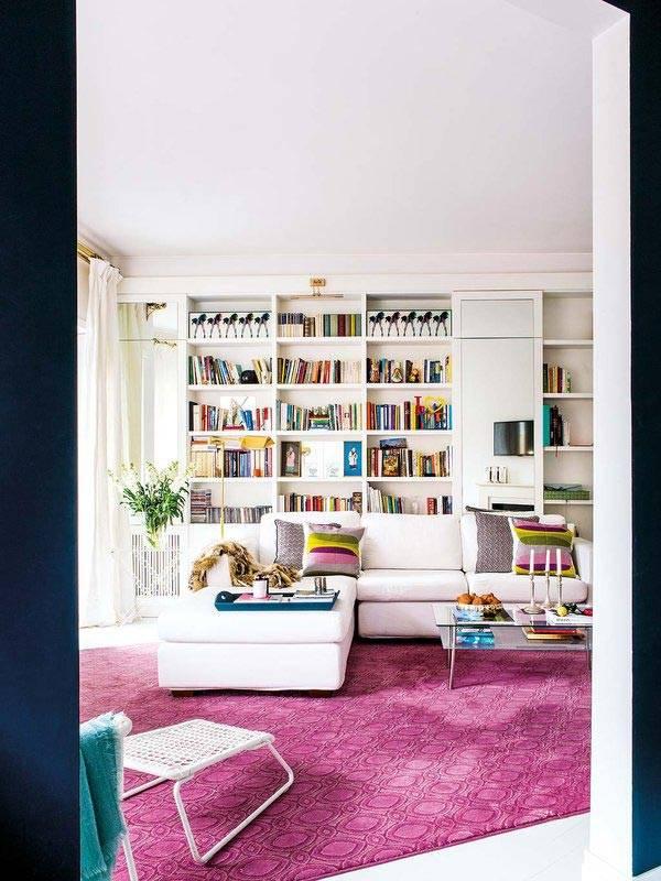 Книжный стеллаж белого цвета вдоль всей стены комнаты