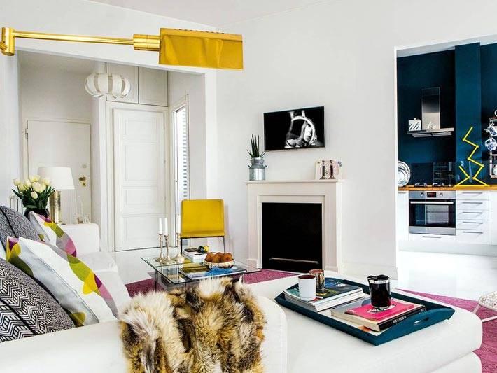 Золотистый бра и желтый стул - акценты в дизайне гостиной комнаты