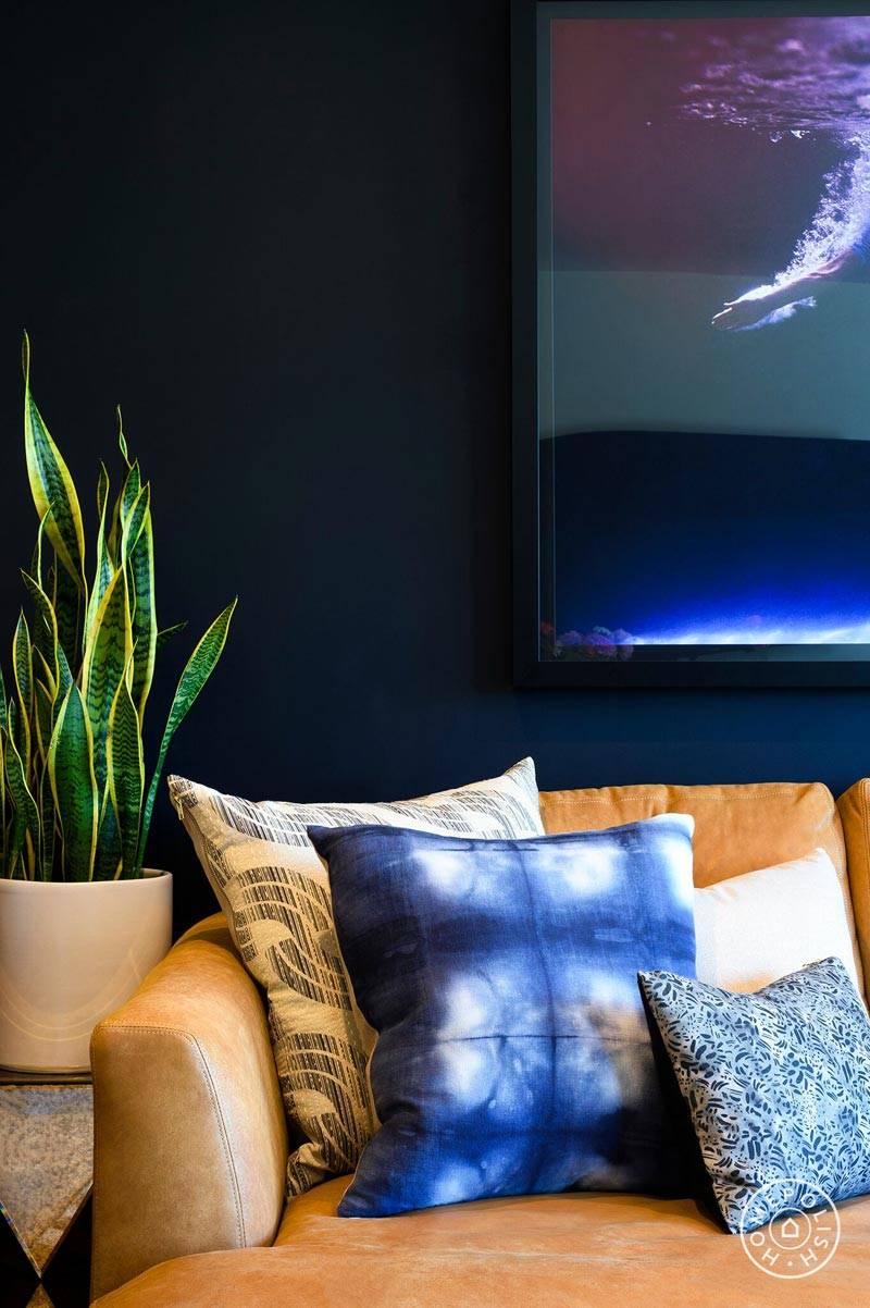 интерьер гостиной с синей стеной и рыжим диваном фото