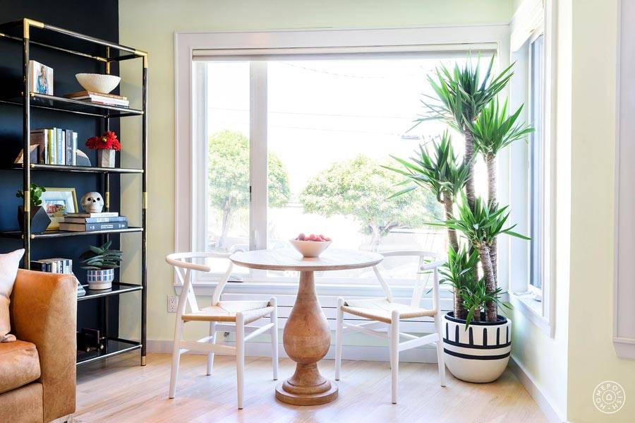 деревянный круглый стол со стульями возле большого окна