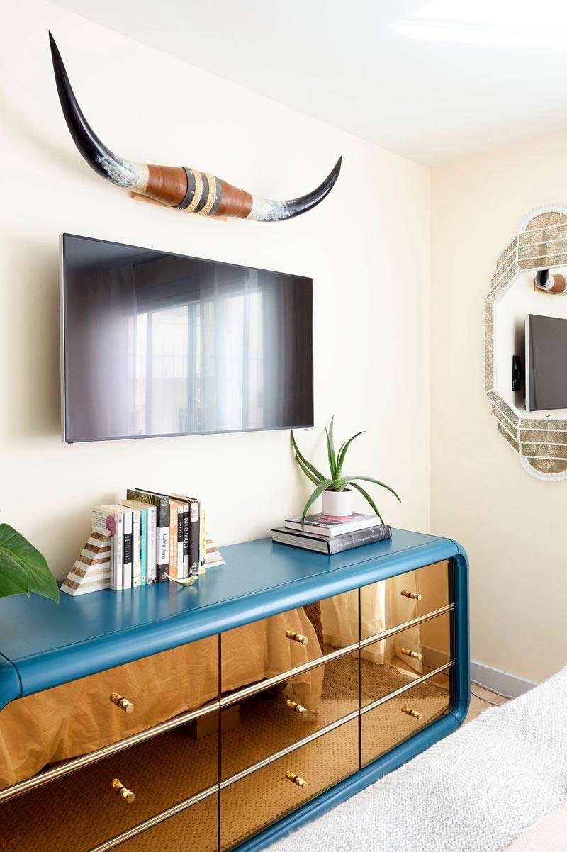 телевизор в спальне и комод с зеркальными ящиками