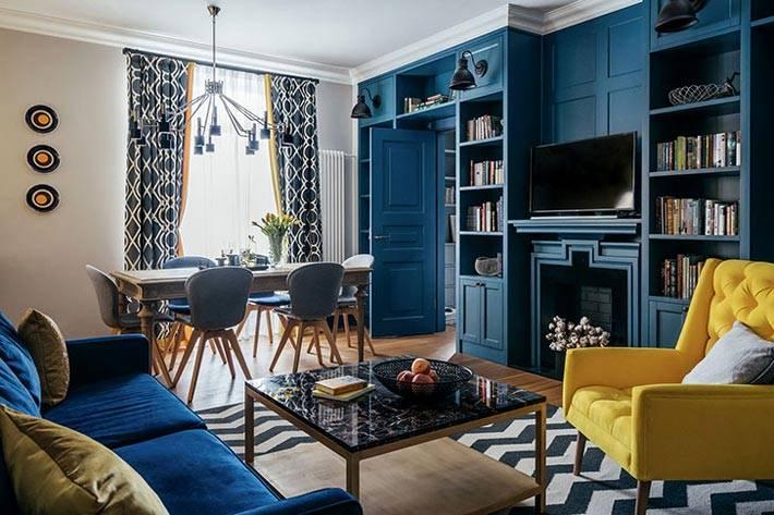 яркое желтое кресло в интерьере гостиной с синими стенами