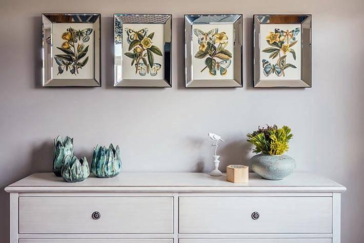 Над белым комодом в спальне висит 4 картины в зеркальных рамах