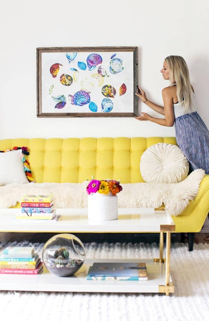 картина с ракушками и желтый диван фото