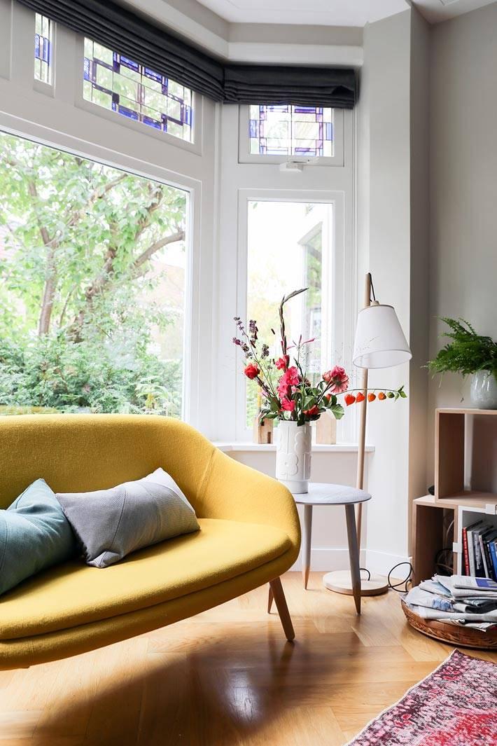 маленький желтый диван в эркере комнаты