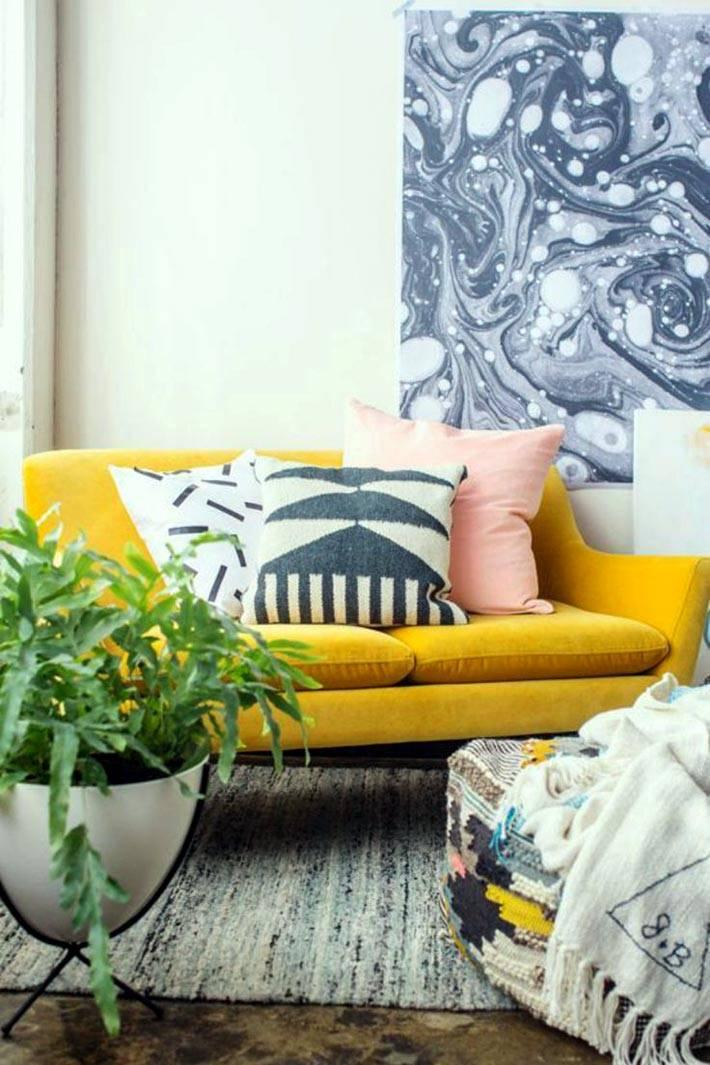 Маленький диван желтого цвета возле окна