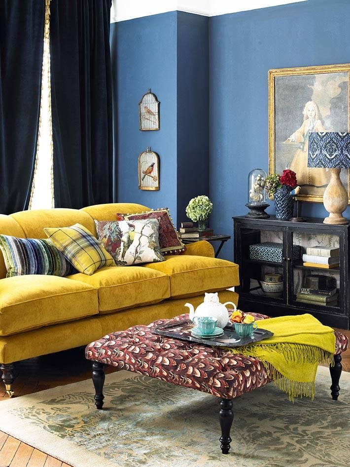 синий интерьер гостиной с ярким желтым диваном