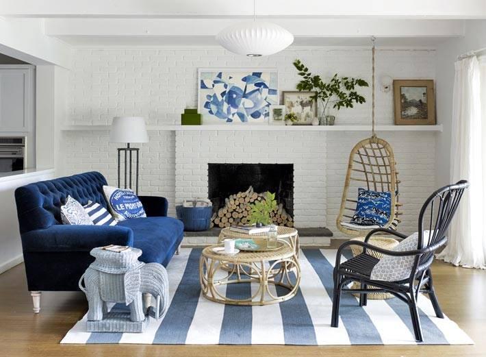 гостиная комната с камином, белой кирпичной стеной и синим диваном