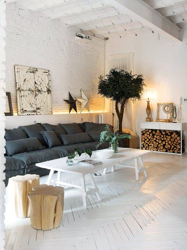 черный диван на фоне белой кирпичной стены в гостиной фото