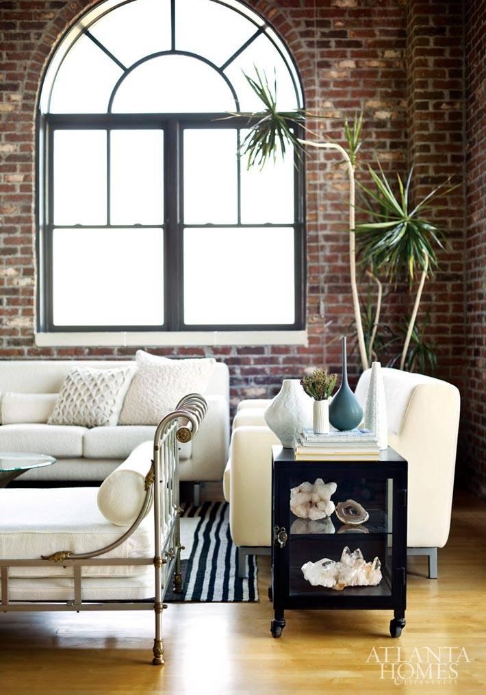 арочное окно на кирпичной стене в гостиной с красивой мебелью