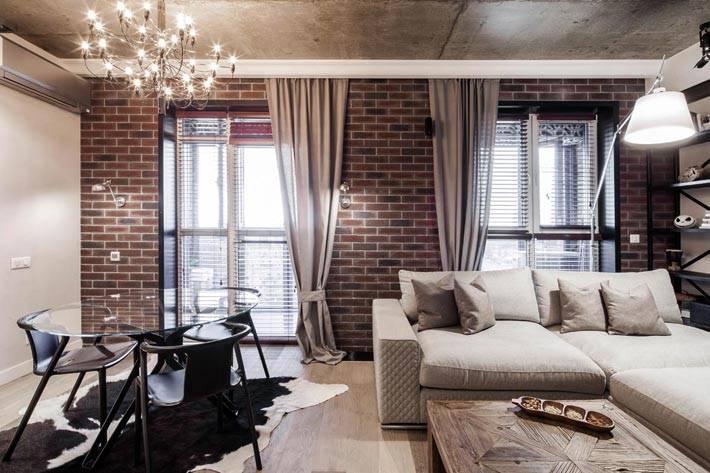 стильный дизайн гостиной с коричневой кирпичной стеной
