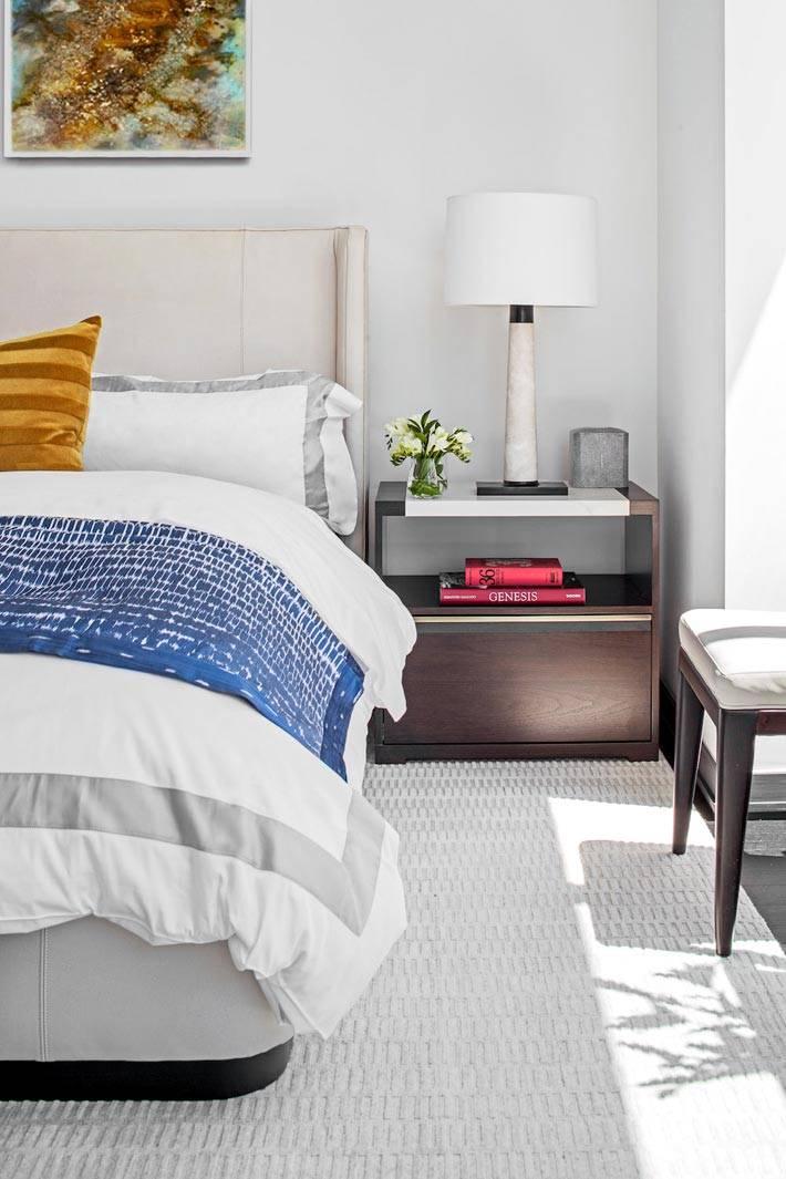 коричневая прикроватная тумба возле белой кровати фото