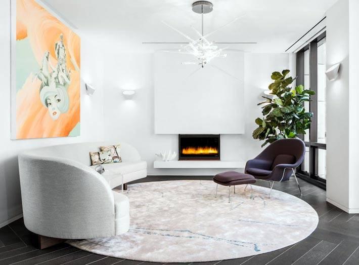 белый интерьер зала с оранжевой картиной и белым диваном