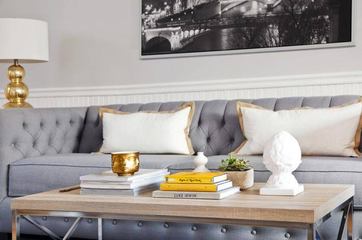 красивый серый диван в гостиной с золотистым декором фото