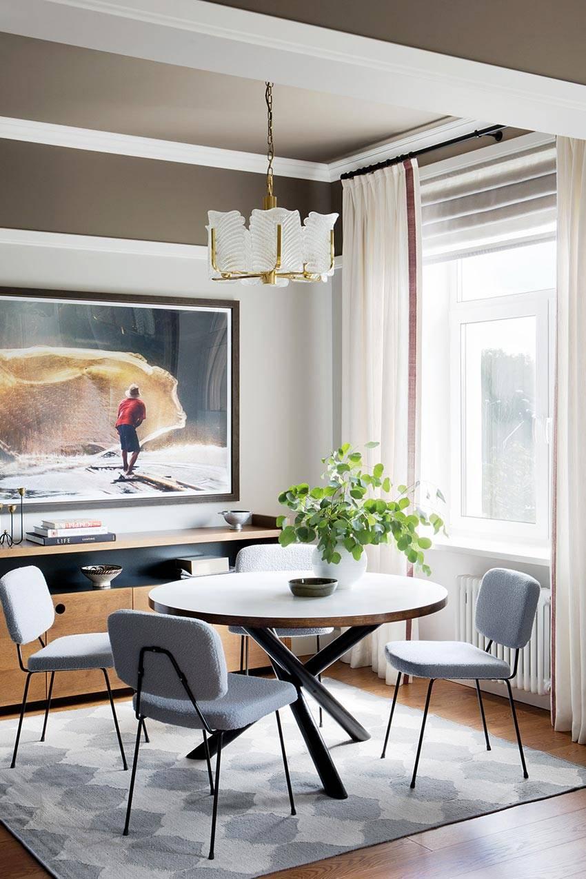 уютная кухня с круглым столом и большой картиной