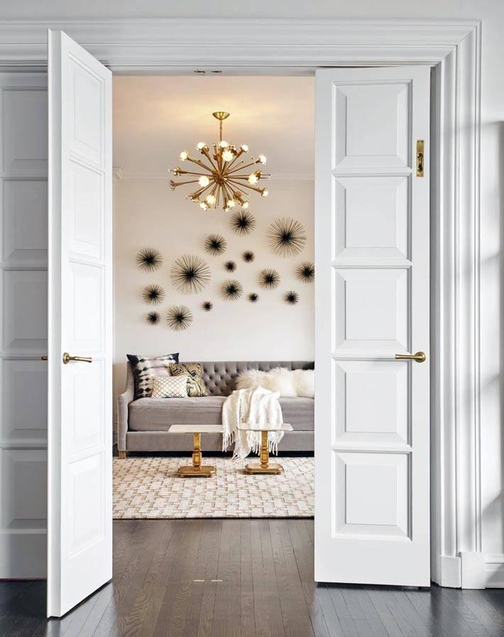 настенный декор с лучами и золотая люстра фото
