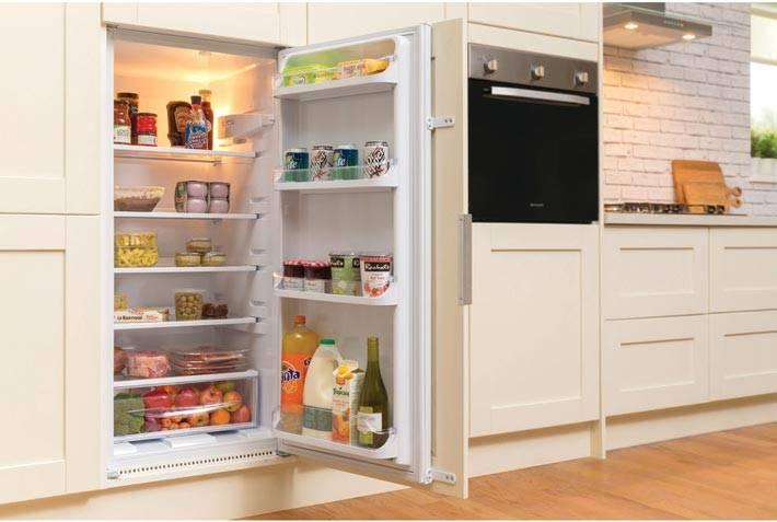 небольшой холодильик, встроенный в белую кухонную мебель фото