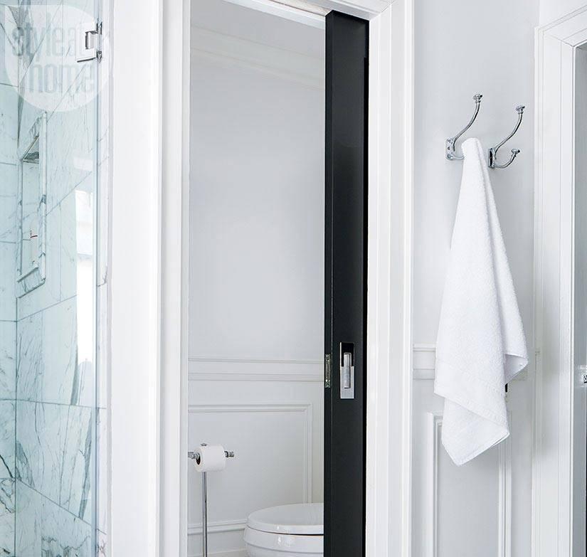 черная дверь в белом интерьере туалетной комнаты