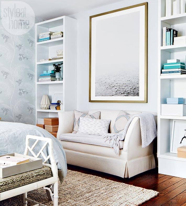 мянкий диванчик в спальне с двумя открытыми стеллажами по бокам