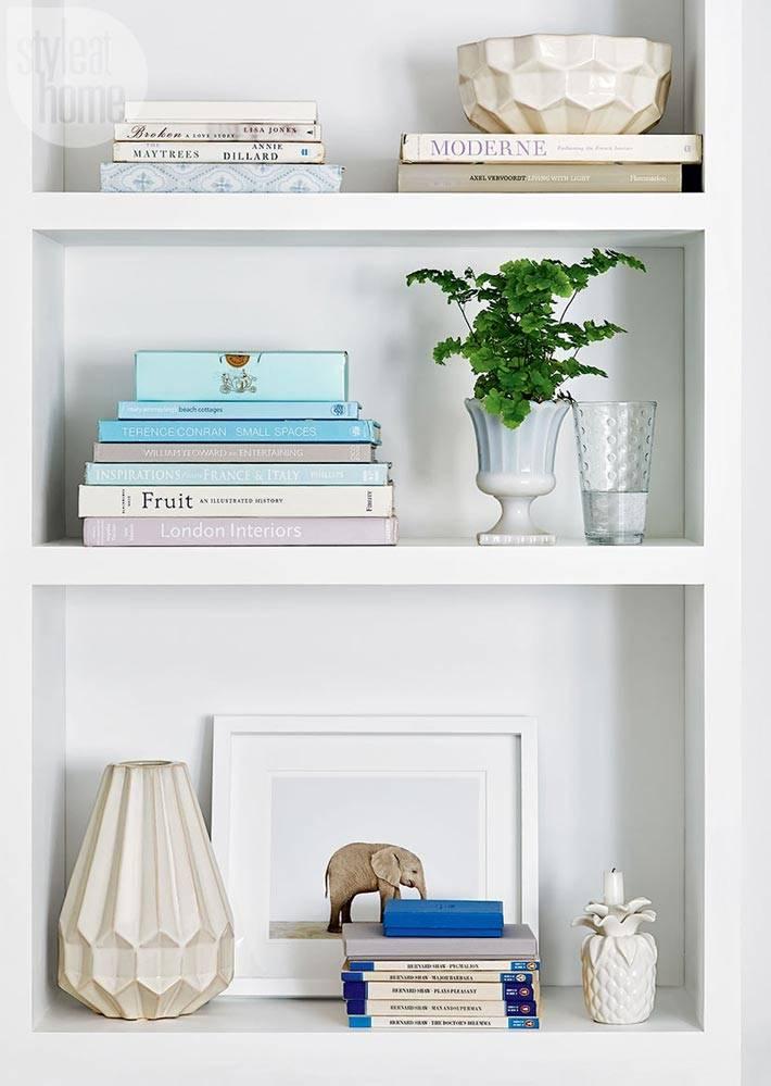 красивый декор из книг и вазочек на открытых полках в спальне