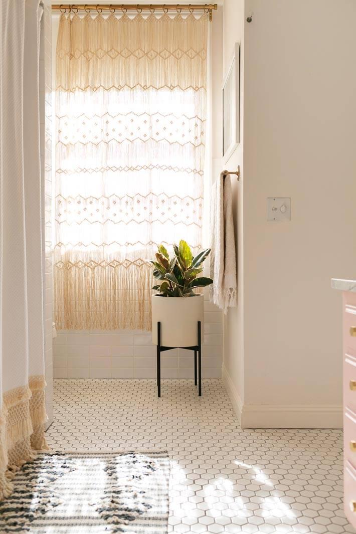 возле окна в ванной комнате стоит горшок с цветком