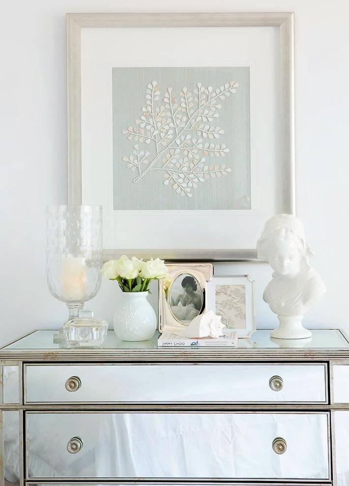 вазы и фото рамы на зеркальном комоде в спальне