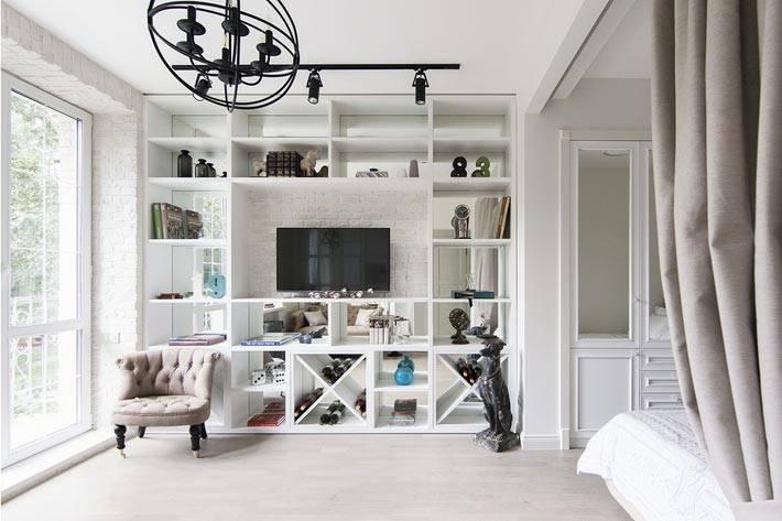 белый стеллаж с полками и телевизором в однокомнатной квартире