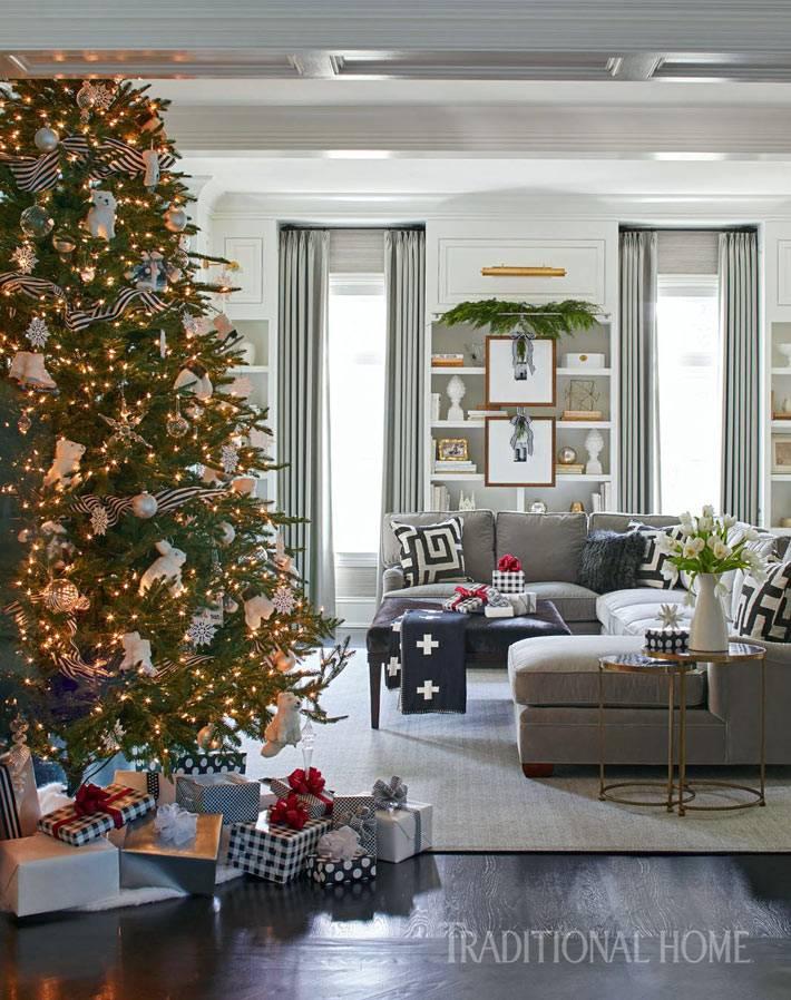 большая елка с игрушками в центре гостиной комнаты фото