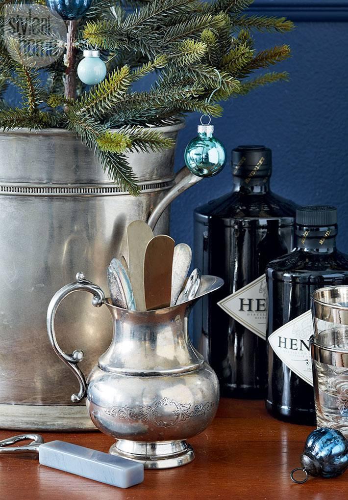 елка в ведру и столовое серебро в графине на новогоднем столе