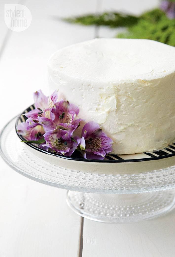 круглый белый торт с фиолетовыми цветами