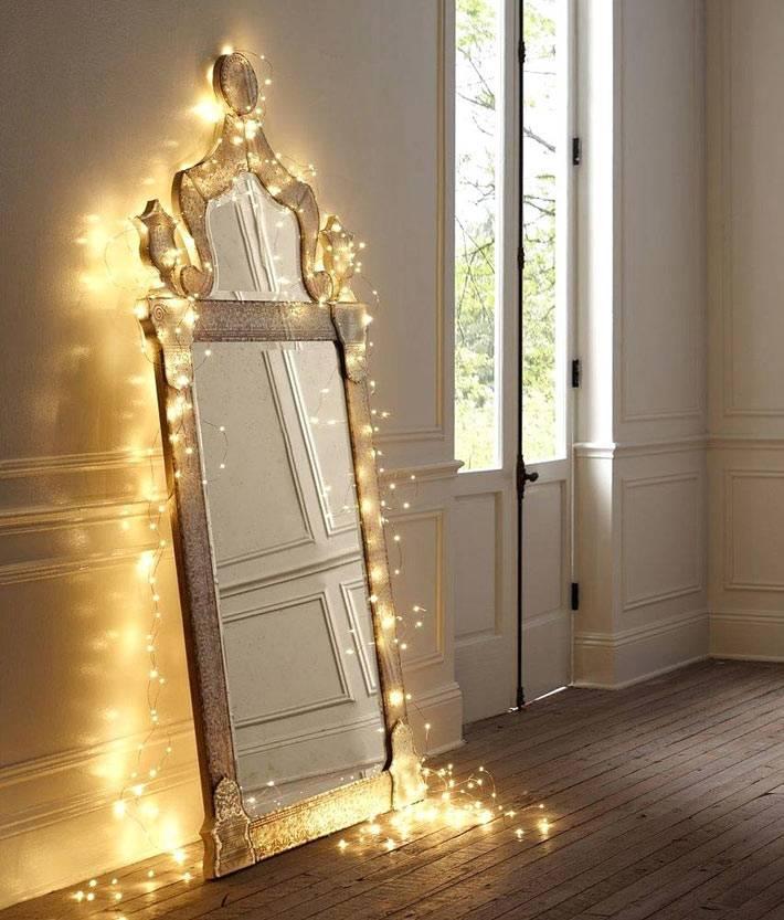 большое зеркало, обвитое новогодней гирляндой фото