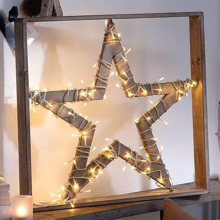 гирлянда вокруг деревянной звезды на новый год фото