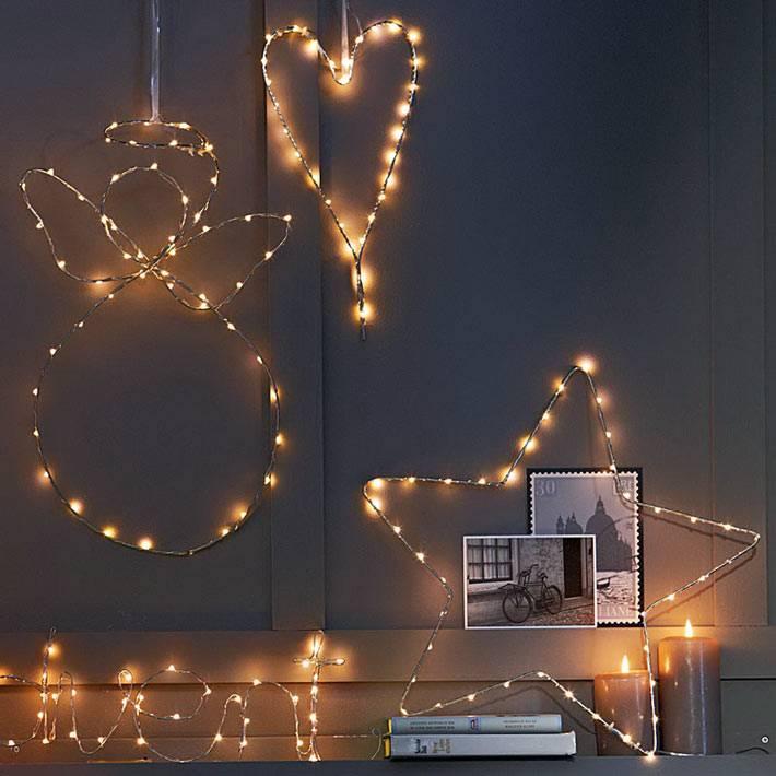 новогодние фигуры из провоочной гирлянды на стене дома