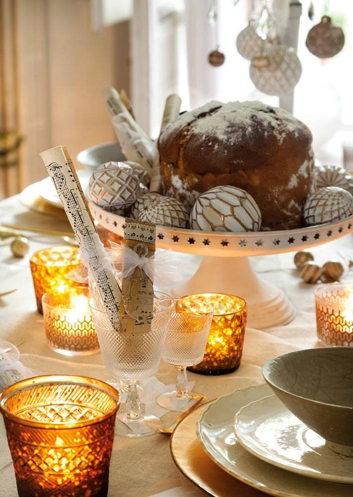 свечи в желтых рифленных стаканах на праздничном столе