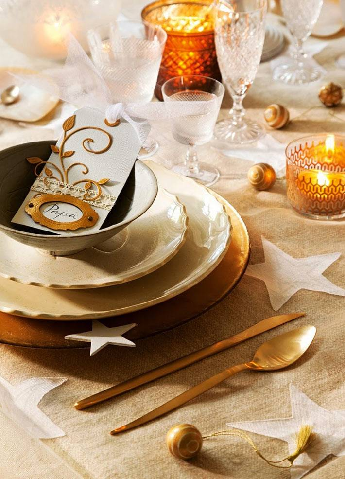 золотистые тарелки, звезды и свечи на новогоднем столе